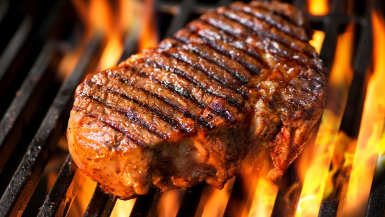 Sizzling steak on a grill