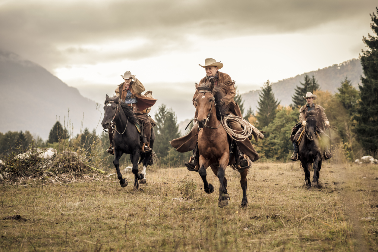 Men and women horseback riding in the mountains